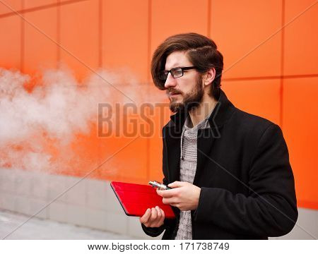 Young hipster man with a beard and glasses smokes an electronic cigarette. He holds a tablet pc.