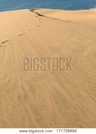 View to sand dune with trace of human footprints on it and sea behind it