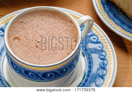 Traditional mexican hot chocolate cup made with cinnamon beaten with wooden utensil called molinillo