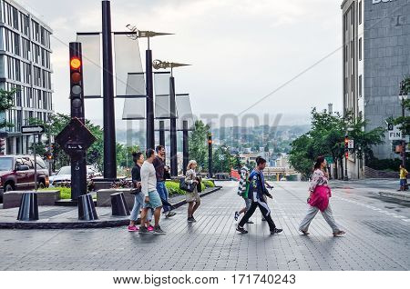 Quebec City, Canada - July 27, 2014: People crossing street on hill with view of suburbs