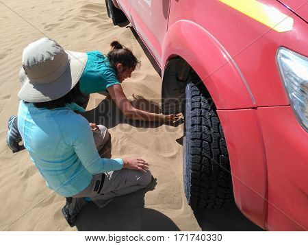PATACHE CHILE 12 JANUARY 2017: women trying to dig out 4x4 which stuck in the sand