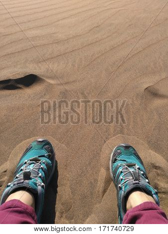 Feet in colorful shoes on the sand of a desert