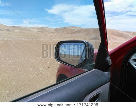 View to the desert from open window of car