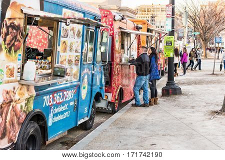 Washington DC, USA - January 28, 2017: Food trucks on street by National Mall with people buying