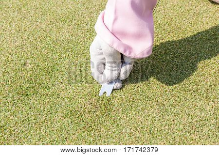 Closeup female staff hand in white glove repairing divot on golf green surface by pitchfork.