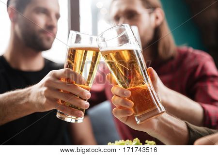 Image of young friends sitting in cafe while drinking alcohol. Focus on glasses of beer.