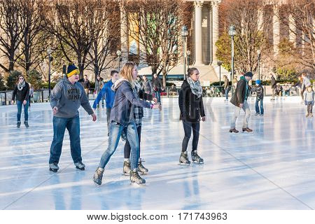 Washington DC, USA - January 28, 2017: Young people skating in ice rink in National Gallery of Art Sculpture garden