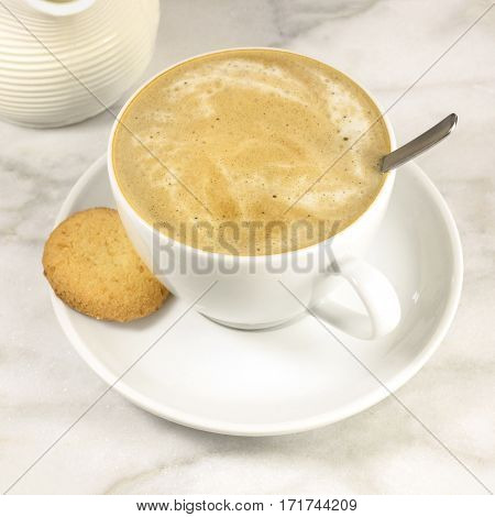 A square photo of a cup of coffee with milk with a butter cookie and a milk jar on a white marble table, with a place for text. Selective focus