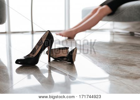 Cropped image of young business woman sitting in office without shoes. Focus on shoes.