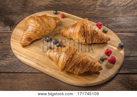 Crunchy French croissants with fresh raspberries and blueberries on a wooden cutting board with copy space