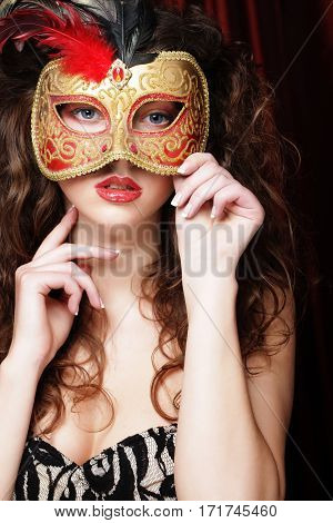 Sexy model woman with venetian masquerade carnival mask at party over holiday red background.