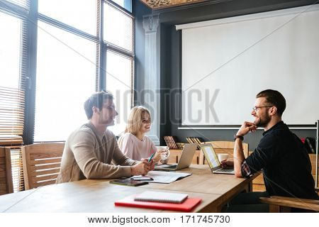 Photo of three young happy colleagues sitting near coffee while work with laptops and notebook. Coworking.