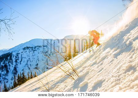 Freerider Skier Descends From The Mountain In The Light Of The M