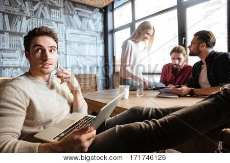 Image of happy colleagues sitting in office and coworking. Working with documents. Talking by phone.