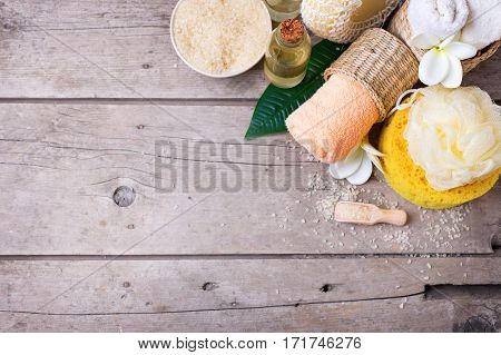 Sea salt towels bottle with aroma oil and wisps on vintage wooden background. Selective focus. Place for text.