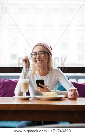 Cheerful young woman in hat and glasses using mobile phone and laughing in cafe