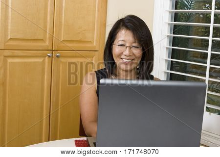 Asian Adult Woman Smiling Using A Laptop in Kitchen.
