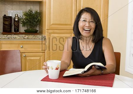 Asian woman reading the Bible in the kitchen.