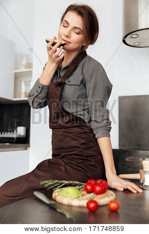 Picture of young lady standing in kitchen cooking with the tomatoes and avocado.