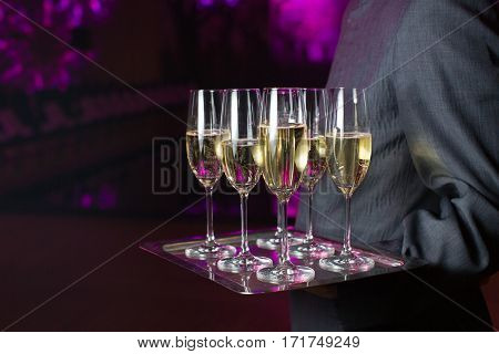 Waiter serving champagne on a tray gala evening