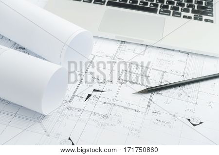 Black Pencil And Computer Laptop On Architectural Drawing Paper For Construction