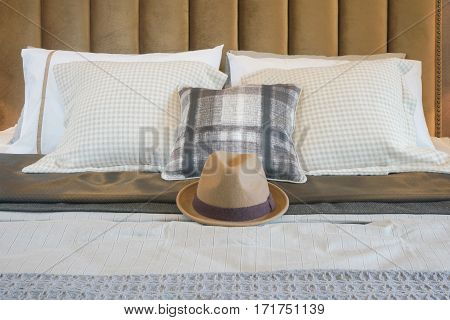 Brown Hat On Center Of Bed With Pillows In Background