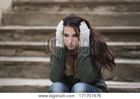 Depressed young woman sitting on stairs