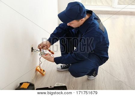 Electrician attaching wires to socket in new building