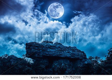 Boulder Against Blue Sky With Clouds And Beautiful Full Moon At Night. Outdoors.