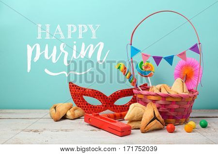 Purim holiday greeting card with hamantaschen cookies and carnival mask over mint background