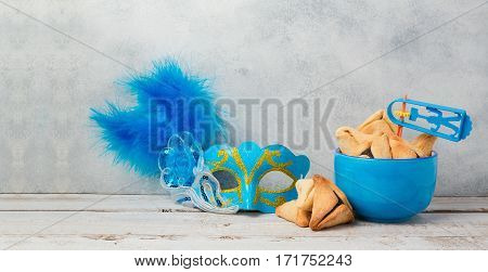Jewish carnival Purim celebration concept with hamantaschen cookies and mask over rustic background