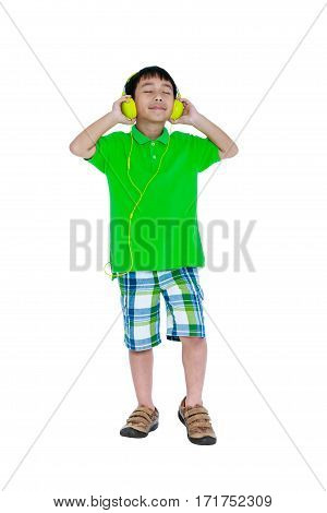 Happy asian child relaxing with headphones Isolated on white background. Cute asian boy enjoying music using earphone. Studio shot. Technology and music concept