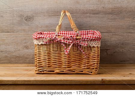 Picnic basket with checked cloth on table over wooden wall background