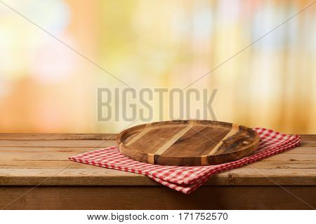 Wooden cutting board with checked tablecloth on table over blurred bokeh background
