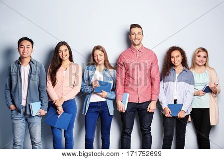 Group of people with books standing near light wall