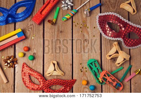 Jewish holiday Purim concept with carnival mask and hamantaschen cookies on wooden background. Top view from above