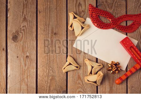 Jewish holiday purim holiday concept with greeting card and hamantaschen cookies on wooden background. Top view from above