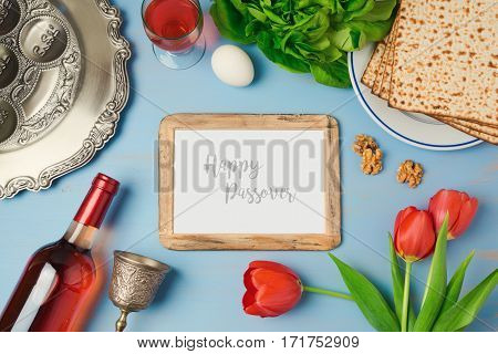 Passover holiday concept with photo frame seder plate and matzoh on wooden background. Top view from above