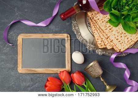 Passover holiday concept seder plate matzoh and chalkboard on dark background. Top view from above