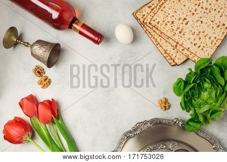 Passover holiday concept seder plate matzoh and wine bottle on bright background. Top view from above