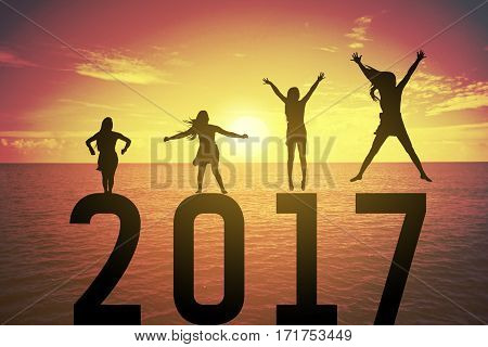 Silhouette young woman jumping and raising up her hand about happy concept on numbers 2017 over a beautiful sunset or sunrise at the sea background for happy news years.success in 2017 years