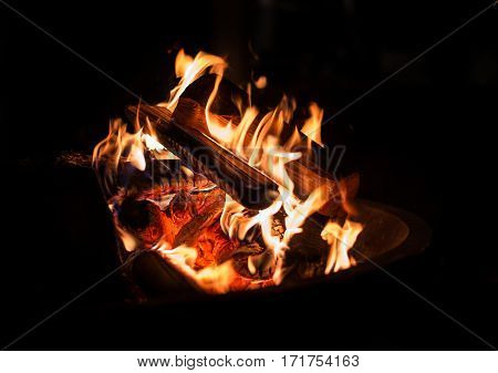 Burning wood - red and orange fire for warming hands on black background