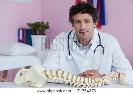 Portrait of physiotherapist sitting with spine model in clinic