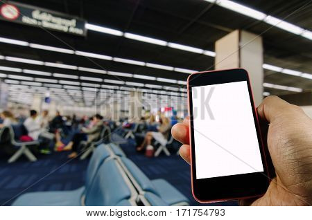 Hand using Smartphone, a blank screen isolated with space for copy on blurred background of passengers waiting bording at airport, color tone effect.