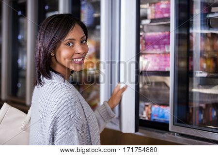 Portrait of smiling woman standing near refrigerator in supermarket