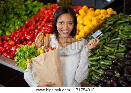 Portrait of woman holding credit card and grocery bag in organic section of supermarket