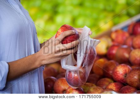 Mid section of woman buying an apple in supermarket