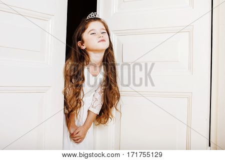 little cute girl at home, opening door well-dressed in white dress, adorable milk fairy teeth, curious child close up