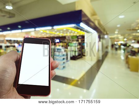 Smartphone in hand with blank screen isolated with space for copy on department store blurred background, business, technology and advertise concept, color tone effect.