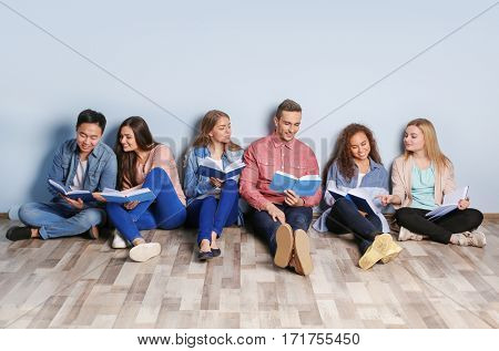 Group of people with books sitting on floor near light wall